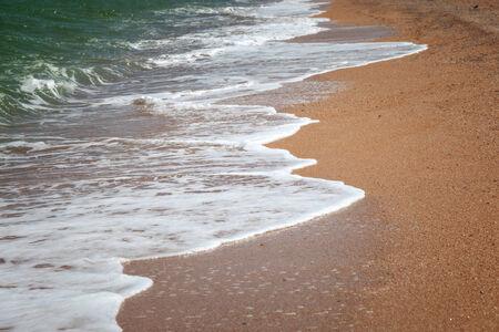foamy: Foamy waves rolling to the sandy beach