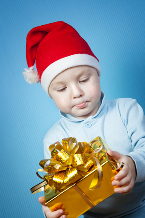 A boy in a cap of Santa Claus with gifts on a blue background photo