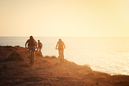 Silhouettes of cyclists on the beach Stock Photo