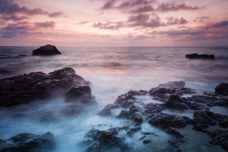 dramatics: Seascape. Seashore with misty water at sunset Stock Photo