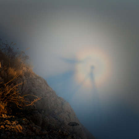 spectre: Silhouette of a man with a rainbow in the clouds (gloria, Brocken Spectre) Stock Photo