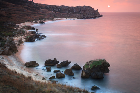 Seascape. Seashore with misty water at sunset Stock Photo
