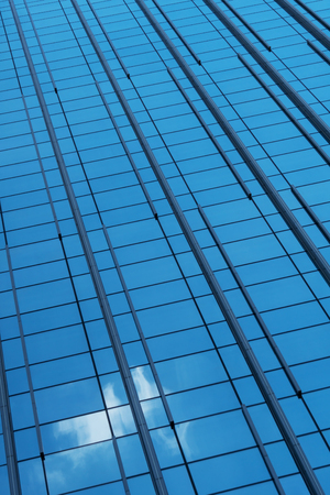 Glass facade of a building with a reflection of the sky with a cloud
