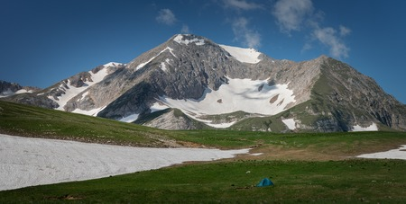 Tourist tent on green grass against the background of high mountains. Lago-Naki. Russia
