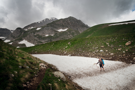 Tourist with a large backpack on the pathway in the background of high snow-capped mountains 版權商用圖片