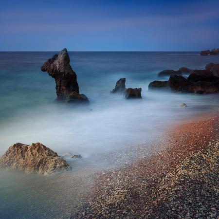 Seascape. Seashore with misty water at sunset 版權商用圖片