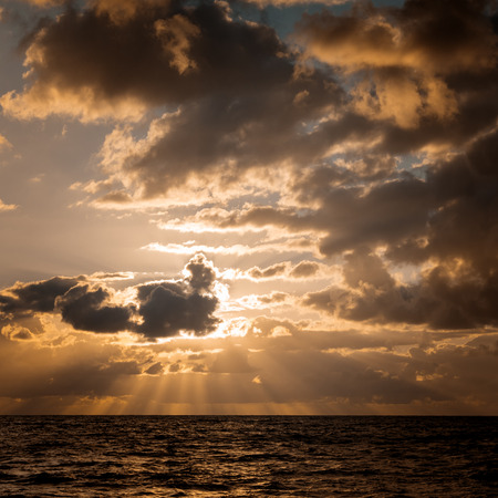 Seascape. Sun in the clouds at sunset over the sea 版權商用圖片