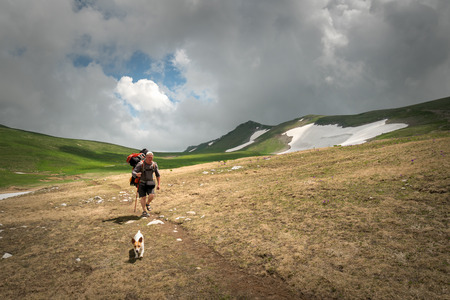 Tourist with a large backpack and a small dog on a hike