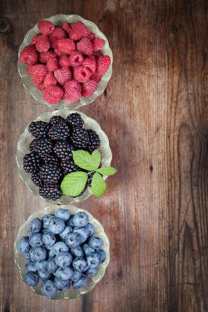 Berries raspberry blackberries blueberries in plates on a wooden table