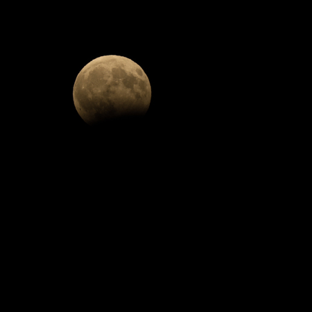 Partial eclipse of the full moon on the night sky 版權商用圖片