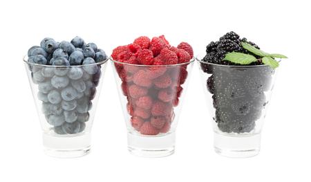 Berry raspberries blackberry blueberries in glass cups isolated on white background 版權商用圖片