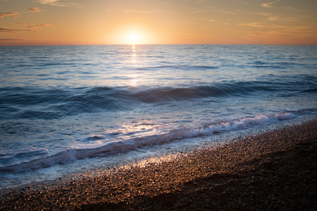 Seascape. Waves on the beach at sunset