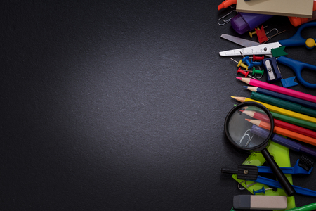 School supplies on the background of a black school board