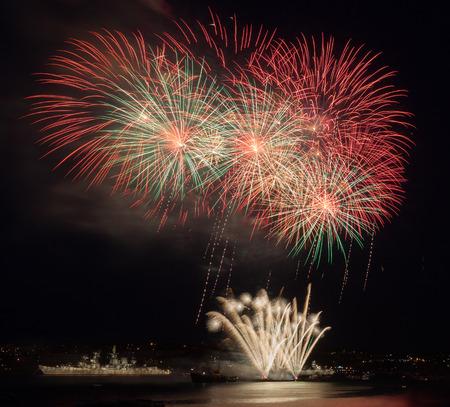Festive fireworks in the night sky above the water 版權商用圖片