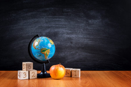 School supplies on the table against the background of the blackboard