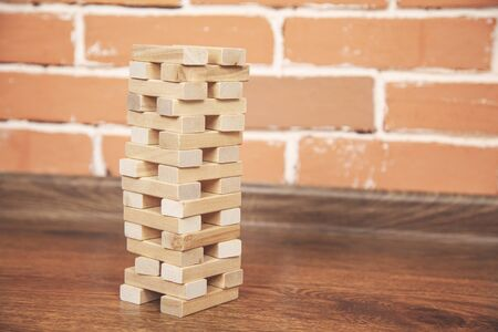 wooden Architectural cubes on table on brick wall background