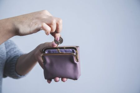 woman hand wallet with coins on gray background
