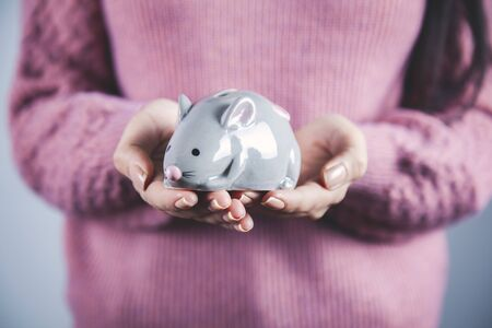 woman hand holding mouse bank on gray background