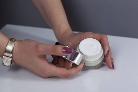 woman hand cream on gray wall background