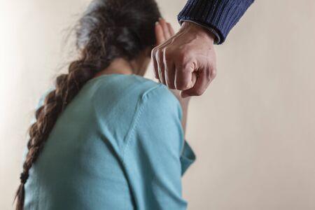 angry man beat sad woman on darkbackground