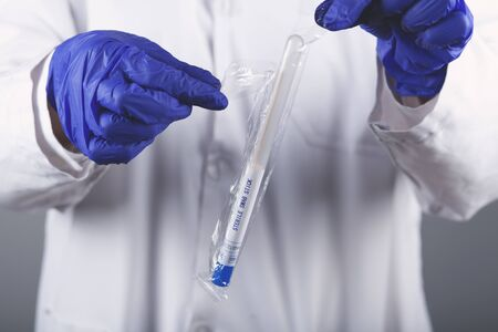 Woman scientists are using aqueous release micro-pipette into the test tube Stock fotó