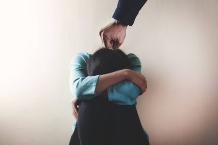 angry man beat sad woman on dark background