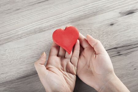 woman hand red heart on the desk background 免版税图像