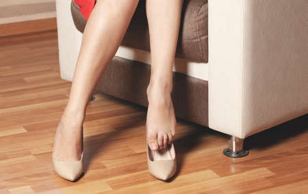woman feet high shoes on armchair