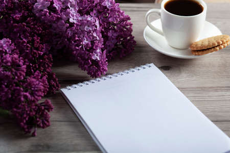 notepad and coffee with lilac on the table