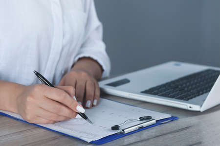 woman hand pen and notepad on gray wall background Фото со стока