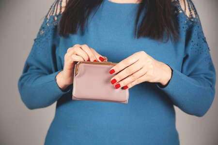 young woman hand holding coin with wallet