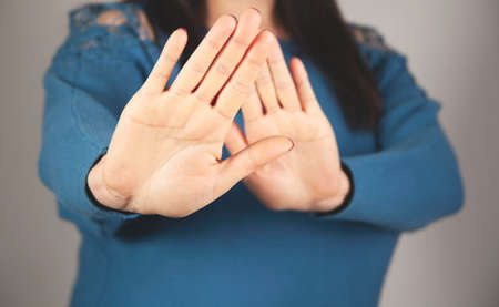 young woman with her hands shows stop on gray background