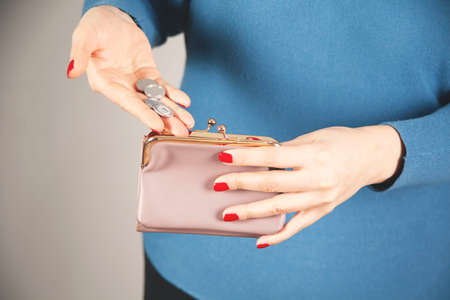 young woman hand holding coin with wallet Stock Photo