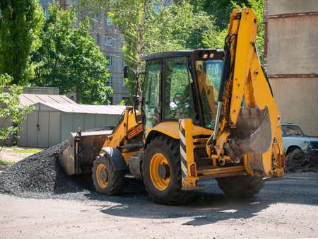Buldozer Making and constructing a new asphalt road near the civil building. Concepts of improvement of the territory of buildings. Housing and utilities concepts Archivio Fotografico