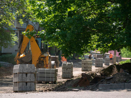 Excavator Making and constructing a new asphalt road near the civil building. Concepts of improvement of the territory of buildings. Housing and utilities concepts