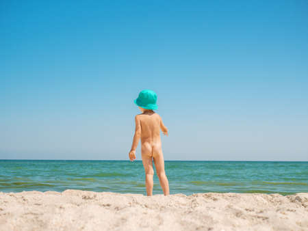 Lilltle boy looking at the ocean, playing on the seaside in summertimes. Baby having fun with the sand. Summer rest concept. Happy childhood concept