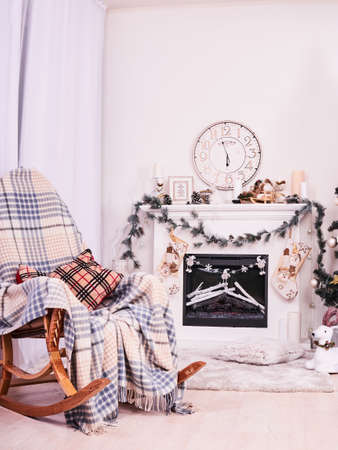 Xmas Fireplace with armchair, clocks and pillows. Christmas stocking over fireplace, New Years card scenery. Snowman and stars. New Year concept