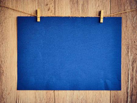 Leer für Text auf blauem Papier einen hölzernen Hintergrund. Brief auf den Wäscheklammern. Vintage Holzbeschaffenheit. Freiraum. Speicherplatz kopieren. Standard-Bild