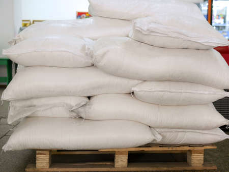 Sugar in bags, stacked on wooden pallet.
