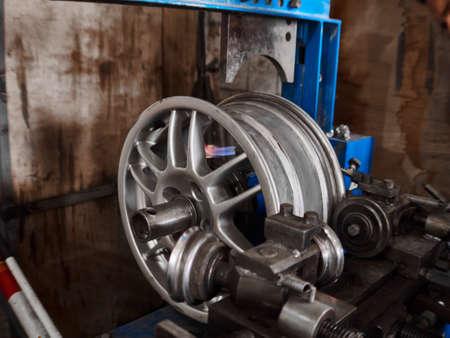 Refurbishment, renewaling and repairing of the alloy aluminium automobile damaged disk at tire service box. 免版税图像