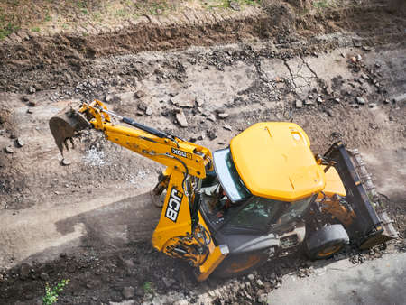 KHARKOV, UKRAINE - MARCH 2020, Buldozer is reconstructing asphalt road near the civil building. Hydraulic Excavator Removing Remains of asphalt. Road reconstruction. Pavement repair.