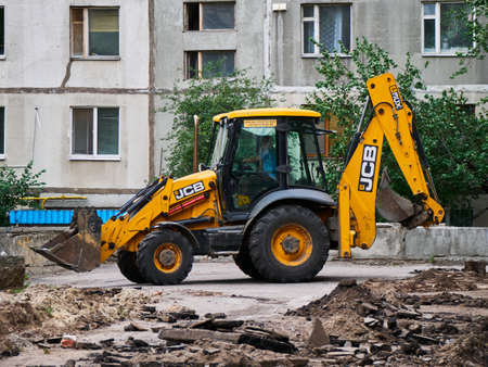 Buldozer Making and constructing a new asphalt road near the civil building. Concepts of improvement of the territory of buildings.