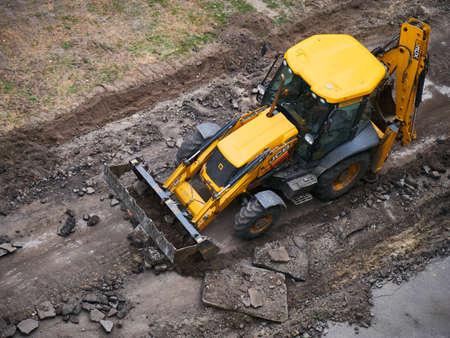 Hydraulic Excavator Removing Remains of asphalt. Road reconstruction, pavement repair