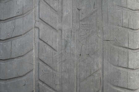 Old black tire with worn tread and cracks, worn old car tire tread, old damaged, worn black tire tread, large cracks in the car wheel, tire black color for background. Foto de archivo - 115232588