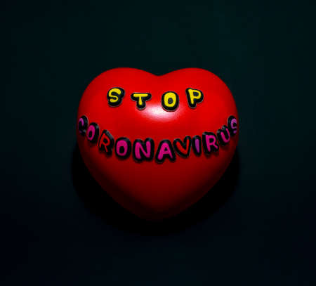 A red heart with the words stop coronavirus on a black background.
