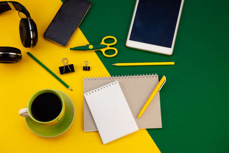 Stationery on the table top view. Yellow and green bright background. Notepad for notes with place for text. Work at home. A cup of coffee. Layout with scissors, pen, notebook. Study and workflow. Stock Photo