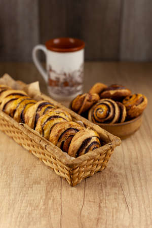 Round homemade cookies on the table. Striped cookies with cocoa and cinnamon. Appetizing rolls for a cup of coffee for breakfast. Wooden background in place for text. Stok Fotoğraf