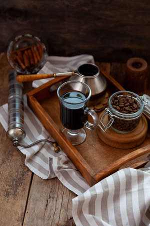 A cup of coffee on a wooden tray. Turk and coffee beans. Cook breakfast at home. Still life with a drink in a glass. Striped tablecloth on a wooden table.