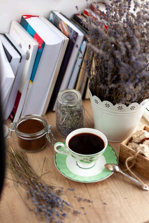Books, coffee and a bouquet of dried lavender. Still life on the table. Breakfast top view. A cup of invigorating drink. Home cozy background. Ground coffee beans in a jar. Dried flowers.