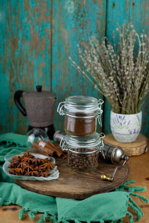 Ground coffee and beans. Breakfast on a wooden table. Cup, glass jars, coffee pot. Still life with a drink on table close up.